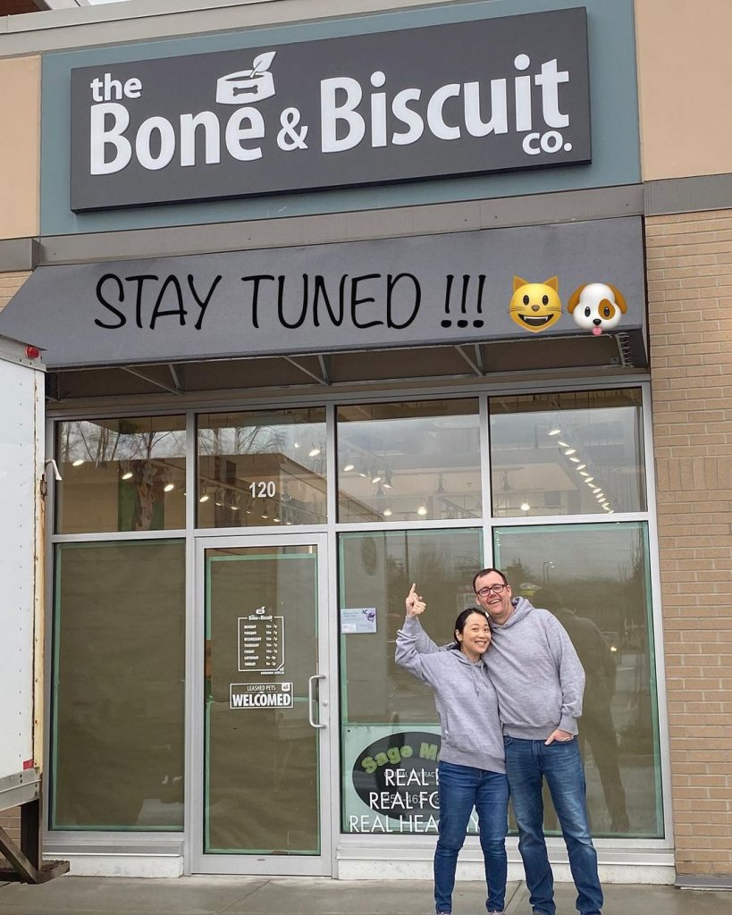 Man and woman in jeans and grey sweatshirts stand outside of The Bone & Biscuit in Maple Ridge