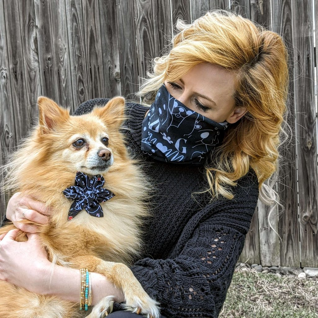 Blonde woman wearing a bandana over her face holds a dog wearing a Huxley & Kent bowtie
