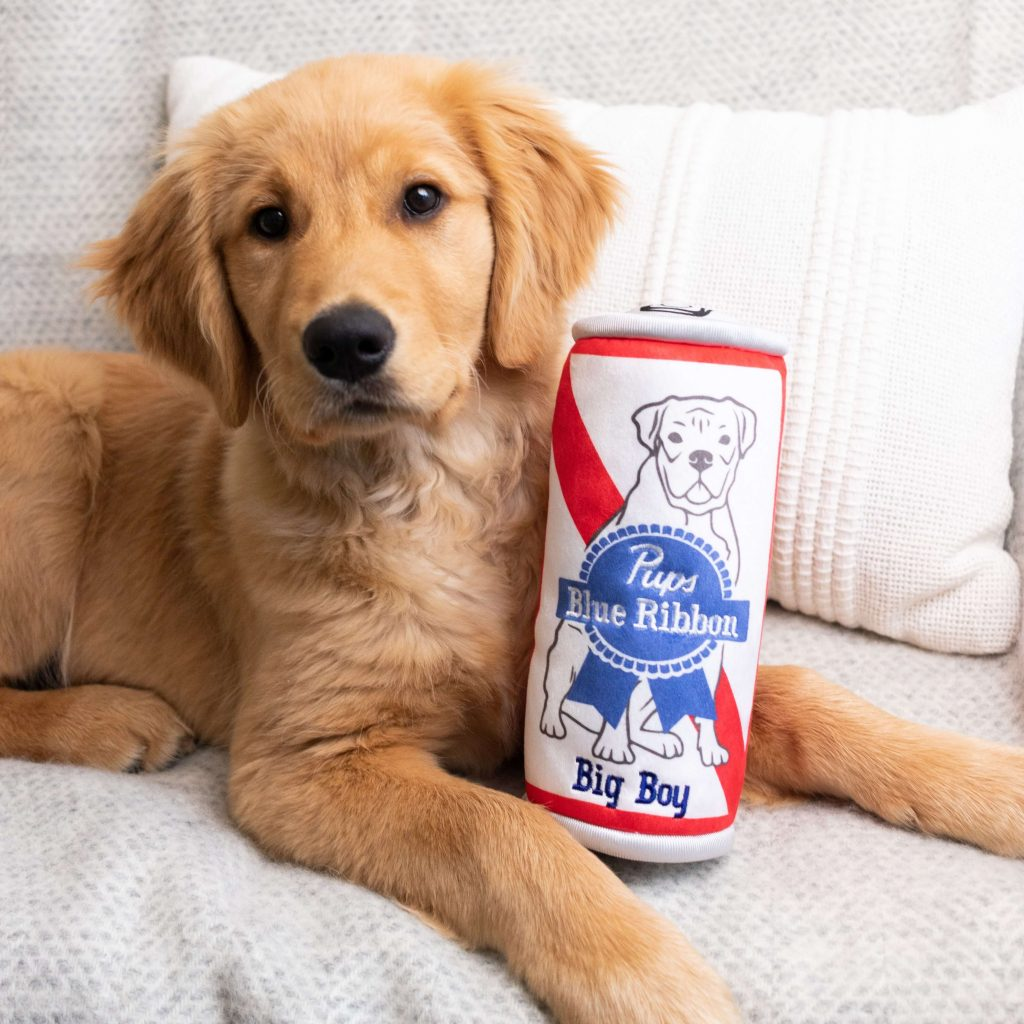 Golden retriever sits with a Huxley & Kent beer can dog toy
